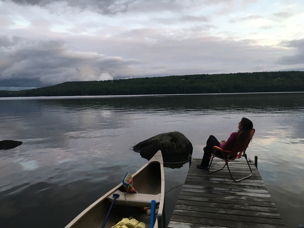 lake with dock and canoe woman on chair